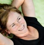 Smiling senior woman lying outdoor. Smiling attractive senior woman lying outdoor on rug Royalty Free Stock Image