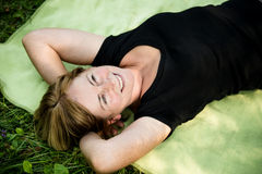 Smiling senior woman lying outdoor. Smiling attractive senior woman lying outdoor on rug in nature Royalty Free Stock Images
