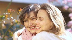 Smiling senior woman and middle aged daughter outdoors closeup portrait stock footage
