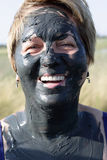 Smiling senior woman with mud face Stock Image
