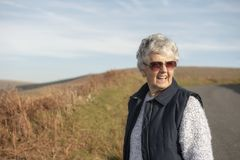 Senior woman outdoors on a sunny day. Smiling senior woman outdoors on a sunny day royalty free stock photos