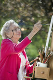 Smiling Senior Woman Painting Stock Photography