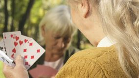 Smiling senior woman playing cards with friend outside, retirement free time. Stock footage stock footage