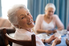 Smiling senior woman playing cards with friends. Smiling senior women playing cards with friends at table in nursing home Stock Photography