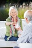 Smiling Senior Woman Playing Cards With Man Stock Image