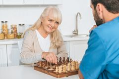 Smiling senior woman playing chess with young. Male nurse stock images