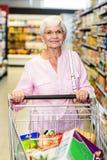 Smiling senior woman pushing trolley Royalty Free Stock Photography