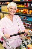 Smiling senior woman pushing trolley Stock Image