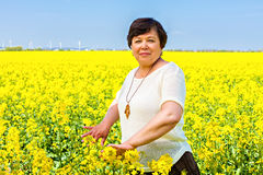 Smiling senior woman in a rape field Stock Photography
