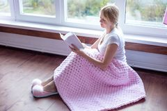 Smiling senior woman reading a book at home royalty free stock photos