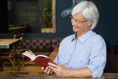 Smiling senior woman reading book while sitting by table. At cafe shop Stock Photo
