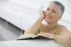 Smiling Senior Woman Reading Book On Sofa Stock Photos