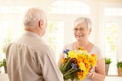 Smiling senior woman receiving bouquet. Of flowers from elderly man Royalty Free Stock Photos