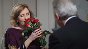Smiling senior woman receiving flowers from man stock footage