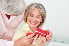 Smiling senior woman receiving gift Stock Photography