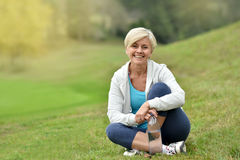 Smiling senior woman relaxing sitting in grass Royalty Free Stock Photography