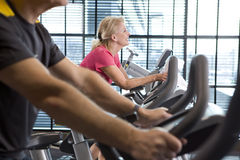 Smiling senior woman riding exercise bike in health club Stock Photography