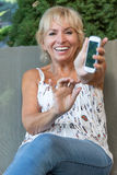 Smiling senior woman is showing her smart phone. Stock Photos