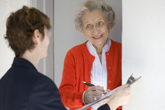 Smiling senior woman signing petetion. Attractive senior woman signing a document at her front door Royalty Free Stock Photo