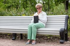 Smiling senior woman sitting long white bench with black book in hand, looking at camera. Smiling senior woman sitting long white bench with black book in hands royalty free stock photos