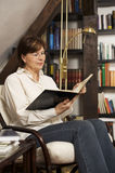 Smiling senior woman sitting and reading a book. Smiling senior woman sitting in chair at home in front of bookshelves reading a book Royalty Free Stock Photo