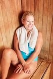 Smiling senior woman relaxing in the sauna. Smiling senior woman sitting relaxed in the sauna at the wellness hotel royalty free stock photos