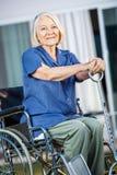 Smiling Senior Woman Sitting On Wheelchair At Yard Stock Photos