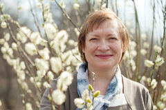Smiling senior woman  in spring willow Royalty Free Stock Photography
