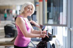 Smiling senior woman standing near barbell in a gym. Stock Photography
