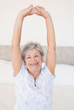 Smiling senior woman stretching on bed Royalty Free Stock Photo