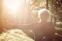 Senior woman stretching hand and exercising in park alon stock photo