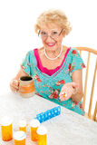 Smiling Senior Woman Takes Medicine. Smiling senior lady cheerfully takes her prescriptions and suppliments.  White background Royalty Free Stock Photography