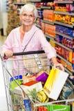 Smiling senior woman taking corn flakes box Stock Photo