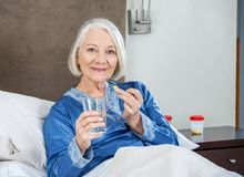 Smiling Senior Woman Taking Medicine At Nursing Stock Images