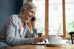 Smiling senior woman talking on mobile phone while working on laptop Stock Photos