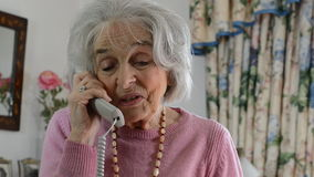 Smiling Senior Woman Talking On The Telephone At Home stock video