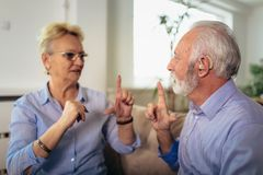 Senior woman talking using sign language with her hearing impairment man. Smiling senior women talking using sign language with her hearing impairment man royalty free stock photo