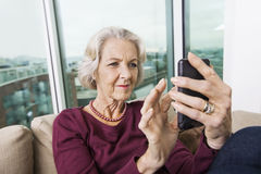 Smiling senior woman text messaging on smart phone at home Stock Images