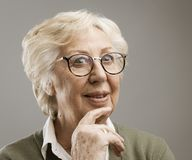 Smiling senior woman thinking with hand on chin. Opportunity and solutions concept royalty free stock photography