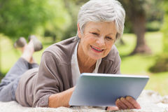 Smiling senior woman using digital tablet at park Royalty Free Stock Photos