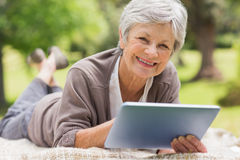 Smiling senior woman using digital tablet at park Royalty Free Stock Images