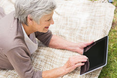 Smiling senior woman using digital tablet at park Stock Images