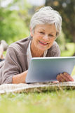 Smiling senior woman using digital tablet at park Stock Photo