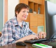 Smiling senior woman using keyboard royalty free stock photo