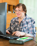 Smiling senior woman using keyboard Stock Images