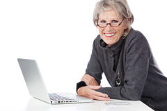 Smiling senior woman using a laptop computer stock images