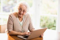 Smiling senior woman using laptop Royalty Free Stock Photos