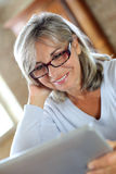 Smiling senior woman using laptop at home Royalty Free Stock Photos