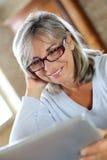 Smiling senior woman using laptop at home Royalty Free Stock Photos