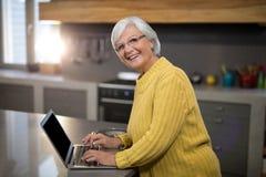 Smiling senior woman using laptop in kitchen. Portrait of smiling senior woman using laptop in kitchen Royalty Free Stock Photo